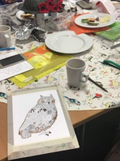 Ink drawing of an owl surrounded by the art table