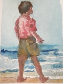 Boy stood on the sand looking out to sea