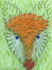 Coloured string wrapped round nails in the shape of a foxes head
