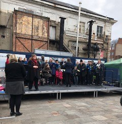 SCL Choir on stage in the Market place, Leicester