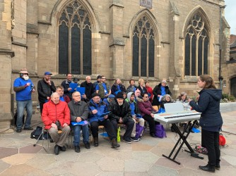 SoundCafe Choir sitting in their coats, Emma conducting them in front of the keyboard. The Choir are in front of the side wall of the Cathedral.